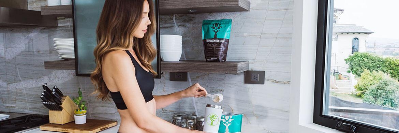 Frau mischt Milch mit Whey Protein