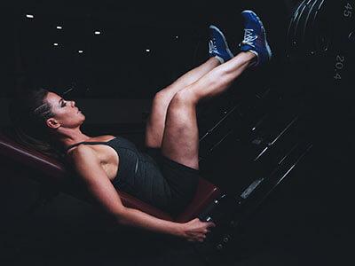Frau trainiert an einer Beinpresse
