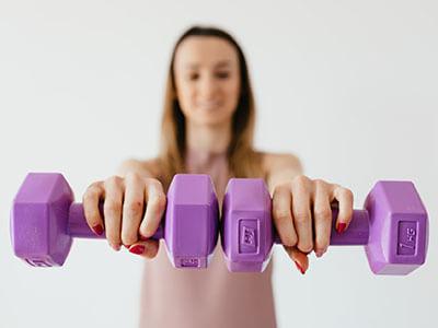 Frau trainiert mit Kurzhanteln